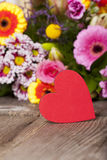 Red heart in front of a bouquet of flowers Stock Photos
