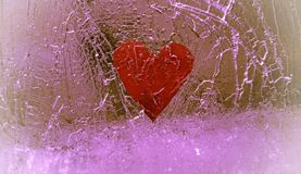 Red heart frozen in cracked ice. royalty free stock photo