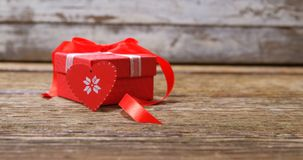Red heart and gift box on wooden surface 4k. Red heart and gift box on wooden surface. Valentines day concept 4k stock video footage