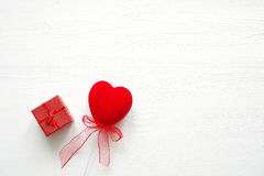 Red heart and gift red box with a bow on a wooden white background. Romantic card. Royalty Free Stock Image