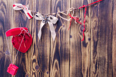 Red heart, gift, white bow and ribbons hanging on a rope Stock Photography