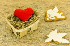 Red heart and ginger biscuits in the form of a cupid and a white dove. Wicker basket and cookies. Stock Photography