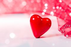 Valentines Day background. A red heart with red glitter textile unfocused background royalty free stock image