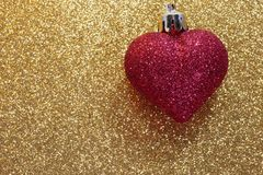 Red heart on golden background shining Stock Photos