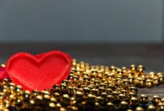 Red heart on the Golden beads.  Royalty Free Stock Photo
