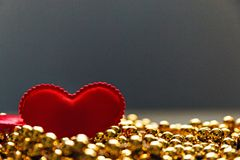 Red heart on the Golden beads.  Stock Photo