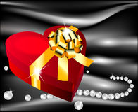 Red heart with golden bow on a background of  silk Royalty Free Stock Photo