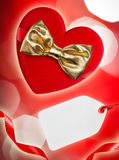 Red heart with golden bow and blank tag, defocused lights on bac Stock Photography