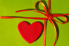 Red heart on a green background with a red tape and a bow Stock Images