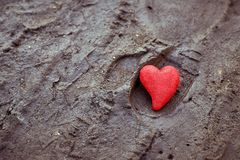 Red heart on the ground. Concept of loneliness, unrequited love stock images