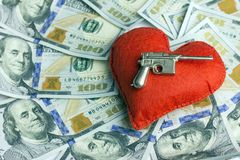 Concept dangerous love for money, Valentine`s Day and weapons. Wedding contract. Thousand US dollars. A red heart and a Royalty Free Stock Photography