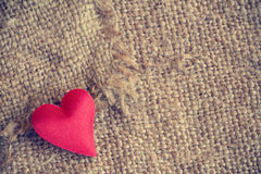 Red heart on gunny sackcloth texture Stock Photo
