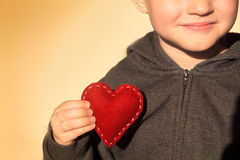 Red heart in hand. Red heart in child hands. Kindness concept, gift, hand made valentine, close up, horizontal, copy space Royalty Free Stock Images