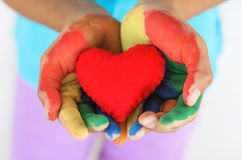 Red heart  hand multi color little girl Stock Photos