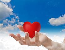 Red heart in hand over blue sky Royalty Free Stock Photography