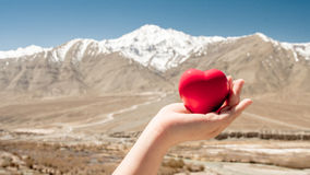 Red heart in hand on white snow mountain. For love valentine`s day background Stock Image