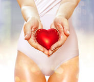 Red heart on hands. Artificial red heart on hands of beautiful woman Royalty Free Stock Photo