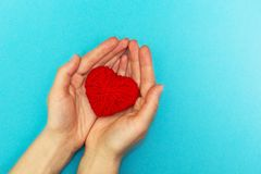Red heart in hands on a blue background royalty free stock image