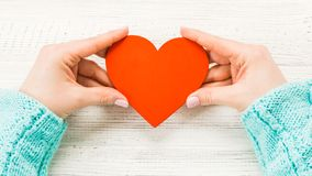Red heart in hands closeup on wooden background. Royalty Free Stock Photography