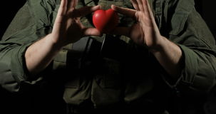 Red heart in the hands of a soldier, concept stock video footage