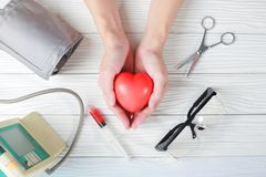 Red heart in hands with stethoscope medical instrument and injec. Tion, syringe on top Royalty Free Stock Images