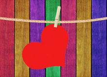 Red heart hang on clothespin over painted wooden background Royalty Free Stock Images