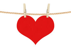 Red heart hang on clothespins isolated on the white Stock Image