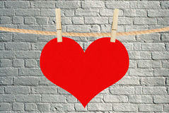 Red heart hang on clothespins over brick background Royalty Free Stock Images