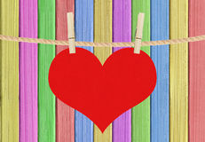 Red heart hang on clothespins over color painted wooden backgrou Royalty Free Stock Image
