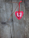 Red heart, hanging on a branch over the grunge wooden background. Royalty Free Stock Photos