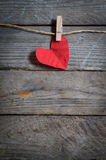 Red heart hanging on the clothesline. On old wood background. Stock Image