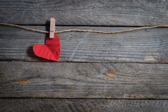 Red heart hanging on the clothesline. On old wood background. Stock Photography