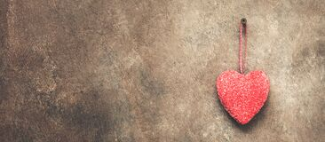 A red heart is hanging on a dark brown rustic wall, border. Valentine`s Day. Copy space. Toned