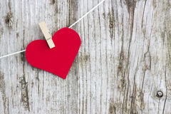Red heart hanging on line. Against old wood-grain wall stock image