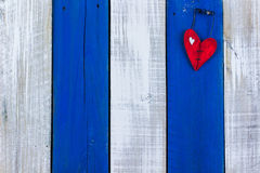 Red heart hanging on rustic door Stock Photo