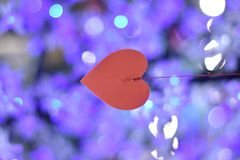 Red heart hanging on a thread on a background of blue lights stock photo