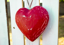 Red heart hanging from white wooden fence Stock Photo
