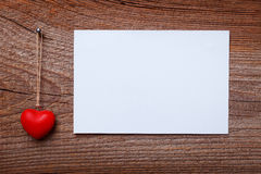 Red heart hanging before wooden board Royalty Free Stock Photos