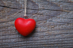 Red heart hanging before wooden board Royalty Free Stock Photography