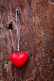 Red heart hanging before wooden board Royalty Free Stock Image