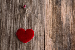 Red heart hanging on wooden texture background Royalty Free Stock Photos