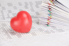 Red heart have blur pile overload paperwork as background. Red heart on finance account have blur pile overload paperwork of receipt and report with colorful Royalty Free Stock Photo