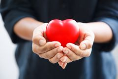 Red heart held by female`s both hands, represent helping hands. Red heart in female`s both hands in black suit background, represents helping hands in hard royalty free stock images