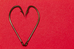 Red Heart of Hooks. A pair of fish hooks forming a heart on red paper Royalty Free Stock Image