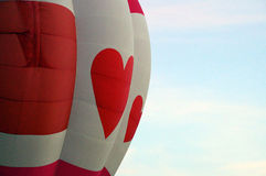 Red heart hot air balloon. Close up of a red and white hot air balloon with hearts against the morning sky Stock Photography
