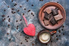 Red heart, hot coffee and chocolate candy on a rustic background. Valentine`s Day. Top view, copy space.  stock image