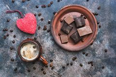 Red heart, hot coffee and chocolate candy on a rustic background. Valentine`s Day. Top view.  royalty free stock photography
