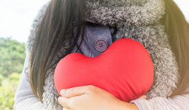 Red heart in hug of women love stock image