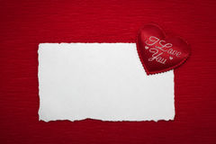 Red heart with an inscription and a white sheet of paper. On a red background Stock Photo