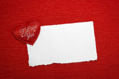 Red heart with an inscription and a white sheet of paper. On a red background Royalty Free Stock Photography